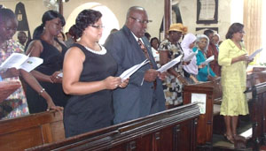 Guyana Consul General to Barbados, Michael Brotherson (second left front row) sings a hymn in the Cathedral Church of Saint Michael and All Angels on Independence Day. To his left is Consulate staff Merlene Gopaul. At far right in the front row is Guyana-born jurist, Justice Maureen Crane-Scott.